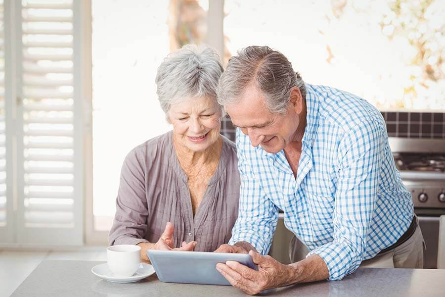 Senior Couple on tablet while having coffee